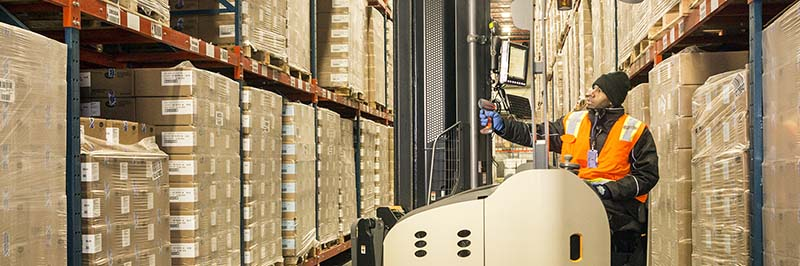 Man Standing On Forklift Inside A Cold Storage Industrial Warehouse