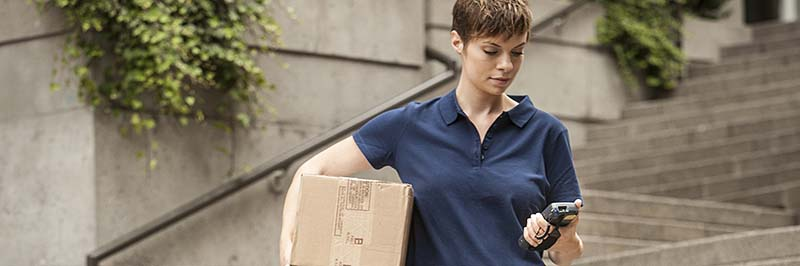 Delivery Woman Carrying Package Down Steps Looking At Handheld Computer